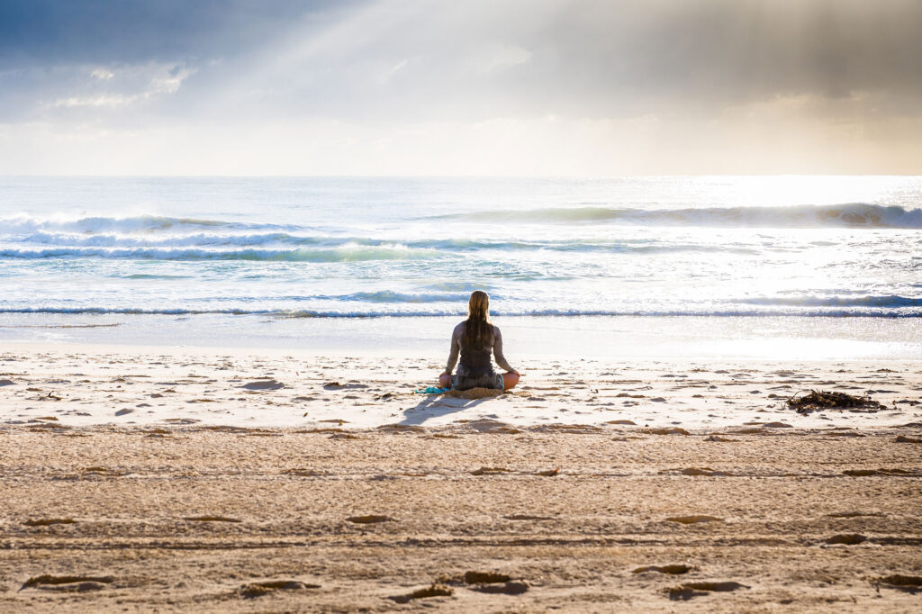 Tranquil woman sitting looking at ocean